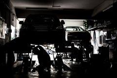 Silhueta dos mecânicos que prestam serviços de manutenção a carros em uma oficina pequena Fotos de Stock Royalty Free