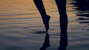 A silhueta dos pés das mulheres vai graciosamente joelho profundamente no lago no por do sol vídeos de arquivo