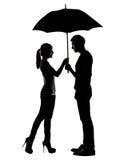 Silhueta dos pares asiáticos que guardam o guarda-chuva Imagens de Stock