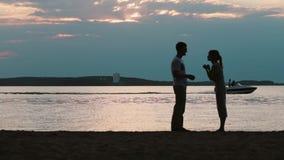 Silhueta dos pares felizes novos que falam na praia Homem e mulher que andam no por do sol, barco a motor no fundo filme