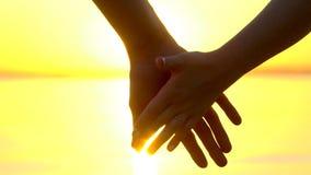 Silhueta dos pares felizes românticos, dos dois amantes, do homem novo e da mulher guardando as mãos na costa do oceano no por do video estoque