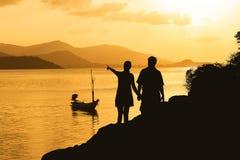 Silhueta dos pares romances que estão em uma rocha Fotos de Stock Royalty Free