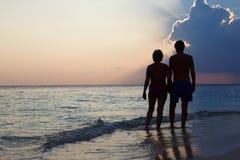 Silhueta dos pares superiores que andam ao longo da praia no por do sol Imagem de Stock