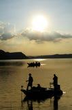Silhueta dos pescadores na água da represa imagens de stock royalty free