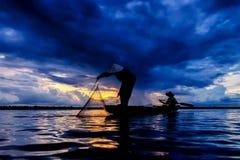 Silhueta dos pescadores tradicionais que jogam o lago líquido da pesca no clound místico no por do sol Fotos de Stock Royalty Free