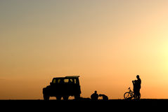 Silhueta dos povos, dos carros e da bicicleta no por do sol Fotografia de Stock Royalty Free