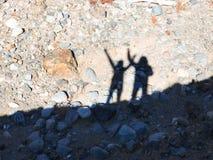 Silhueta dos povos que cumprimentam o sobre o fundo natural na montanha foto de stock
