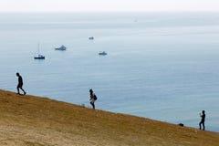 Silhueta dos povos que escalam os penhascos de giz brancos no Seve Fotografia de Stock