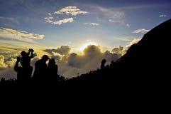 Silhueta dos povos que tomam uma foto do por do sol na montanha Imagens de Stock Royalty Free