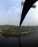 Silhueta dos povos que viajam através da ponte imagem de stock