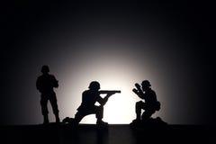 Silhueta dos soldados em um fundo escuro Foto de Stock