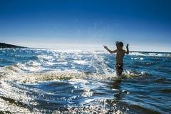 A silhueta e a água da criança espirram no mar. Vacati das horas de verão Fotografia de Stock Royalty Free