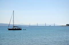 Silhueta e veleiro da ponte de Charilaos Trikoupis imagem de stock royalty free