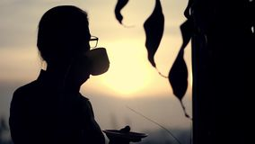 Silhueta escura da mulher de negócio nos vidros, café bebendo no fim do dia de trabalho, mantendo um copo nas mãos, contra filme