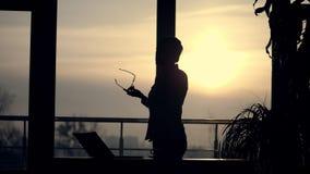 Silhueta escura da mulher de negócio nova guarda vidros em sua mão, negociações emocionalmente no telefone celular, gesticula filme