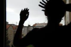 Silhueta fêmea pela janela Imagens de Stock