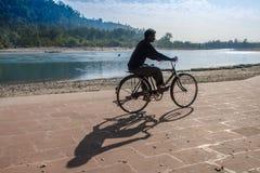 Silhueta indiana não identificada do homem que monta uma bicicleta sobre com uma sombra nos ghats de Ganga fotografia de stock