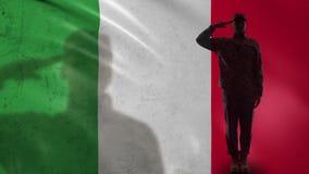 Silhueta italiana do soldado que sauda contra a bandeira nacional, oficial de exército orgulhoso video estoque