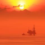 Silhueta Jack Up Drilling Rig a pouca distância do mar e barco Imagens de Stock Royalty Free