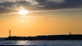 Silhueta masculina em rochas, no nascer do sol, na costa do mar ou do oceano imagens de stock