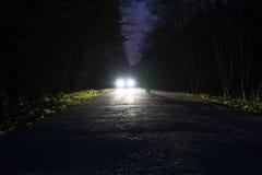 Silhueta masculina na borda de uma estrada escura da montanha através da floresta na noite Homem que está na estrada contra foto de stock