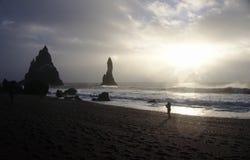 Silhueta na frente das ondas na costa da praia preta da areia, Islândia foto de stock