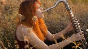 Silhueta na menina ruivo bonita nova do por do sol que joga a natureza do saxophoneon, uma mulher que funde na tubulação, passate video estoque