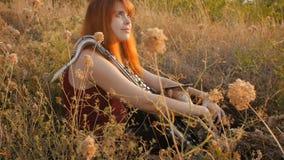 Silhueta na menina ruivo bonita nova do por do sol que joga a natureza do saxophoneon, uma mulher que funde na tubulação, passate filme
