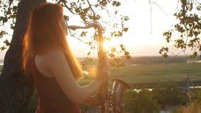 Silhueta na menina ruivo bonita nova do por do sol que joga a natureza do saxophoneon, uma mulher que funde na tubulação, passate vídeos de arquivo