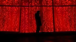A silhueta na noite na perspectiva das festões, uma pessoa está na rua Conceito do ano novo foto de stock royalty free