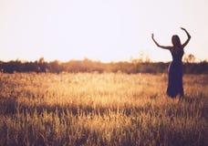 Silhueta obscura da mulher da dança contra o céu do por do sol Imagens de Stock Royalty Free