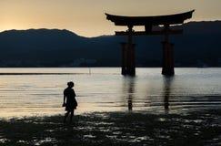 Silhueta perto de Torii - porta de flutuação da mulher gravida da ilha de Miyajima (Itsukushima) no tempo do por do sol fotografia de stock