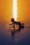 Silhueta preta da criança pequena na praia molhada do por do sol imagem de stock