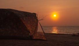 Silhueta que acampa na praia no por do sol Fotografia de Stock Royalty Free