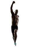 Silhueta running de salto do homem muscular africano novo da construção fotografia de stock