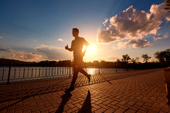 Silhueta running do homem no tempo do por do sol fotografia de stock royalty free