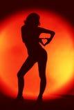 Silhueta 'sexy' da mulher no fundo vermelho fotos de stock royalty free