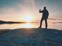 Silhueta traseira do homem de viagem que toma o selfie no mar Turista com a trouxa que está em uma rocha imagens de stock royalty free