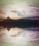 A silhueta triste do menino preocupou-se no prado no por do sol com água com referência a imagem de stock royalty free