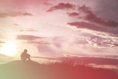 A silhueta triste do menino preocupou-se no prado no por do sol, silhueta c Fotografia de Stock Royalty Free