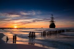 Silhueta velha do navio no cenário do por do sol foto de stock