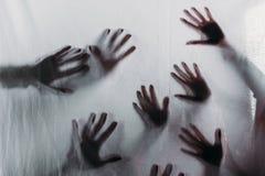 silhuetas assustadores obscuras das mãos humanas que tocam no vidro geado foto de stock royalty free