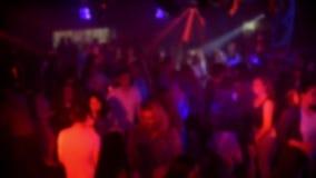Silhuetas borradas de uma multidão de povos de dança em um clube noturno em um partido vídeos de arquivo