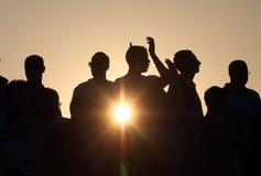 Silhuetas Cheering no por do sol Imagens de Stock
