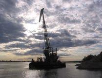 Silhuetas da barca dos guindastes contra o céu no por do sol imagem de stock