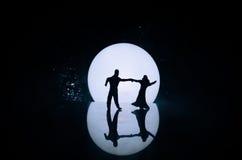 Silhuetas da dança dos pares do brinquedo sob a lua na noite Figuras do homem e da mulher na dança do amor no luar Fotos de Stock Royalty Free