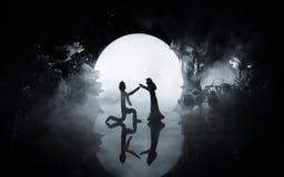 Silhuetas da dança dos pares do brinquedo sob a lua na noite Figuras do homem e da mulher na dança do amor no luar Imagem de Stock Royalty Free