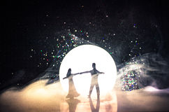 Silhuetas da dança dos pares do brinquedo sob a lua na noite Figuras do homem e da mulher na dança do amor no luar Fotos de Stock