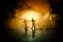 Silhuetas da dança dos pares do brinquedo sob a lua na noite Figuras do homem e da mulher na dança do amor no luar Foto de Stock