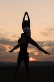 Silhuetas da dança ginástica misturada bonita dos pares no por do sol Grace e beleza do corpo de ser humano Fotografia de Stock